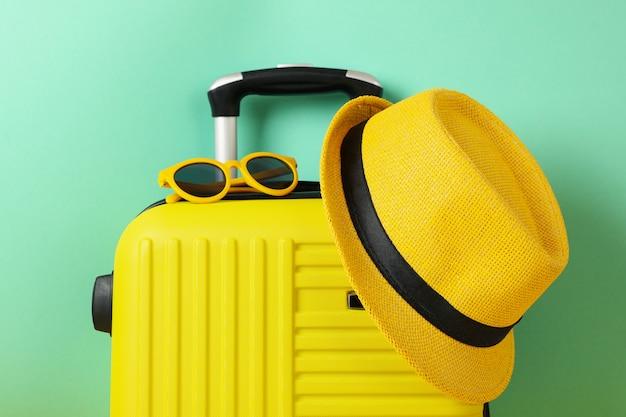 Mala de viagem com óculos escuros e chapéu em hortelã