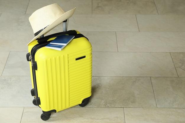 Mala de viagem com passaporte e chapéu, espaço para texto