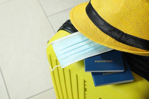 Mala de viagem com passaportes, máscara médica e chapéu