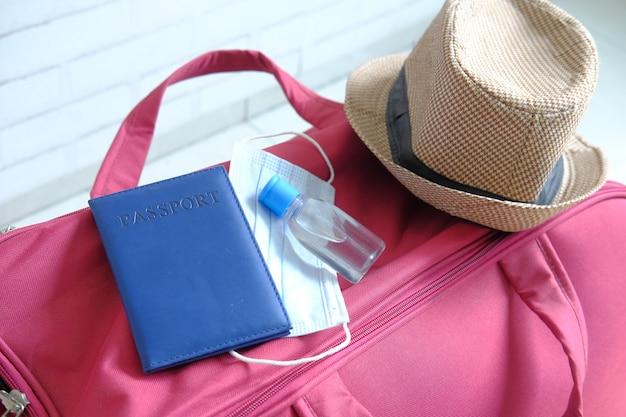 Mala de viagem com uma máscara de passaporte e desinfetante para as mãos