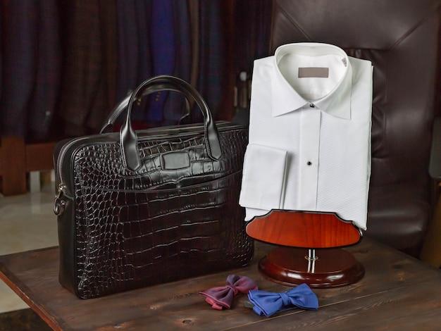 Mala de viagem de couro de crocodilo para homens, ao lado de uma camisa branca e gravatas-borboleta