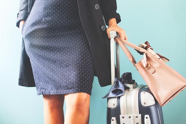 Mala de viagem e bolsa de viagem levando da mulher de negócios no fundo azul da cor, seção mestra.