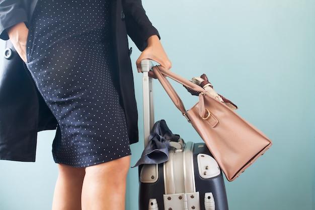 Mala de viagem levando da bagagem da mulher de negócios nova e esperta. meio. conceito de viagens de negócios