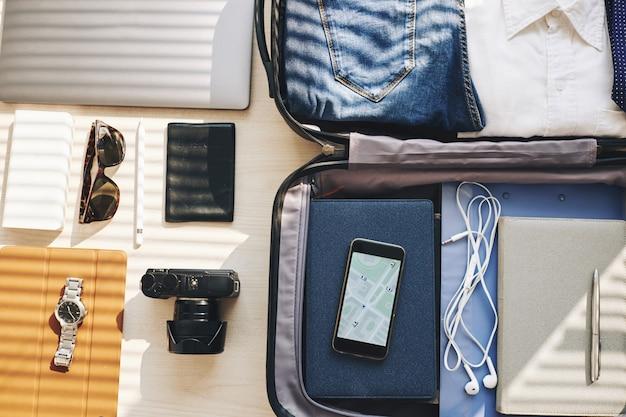 Mala, dispositivos eletrônicos e objetos pessoais organizados para viagens de negócios