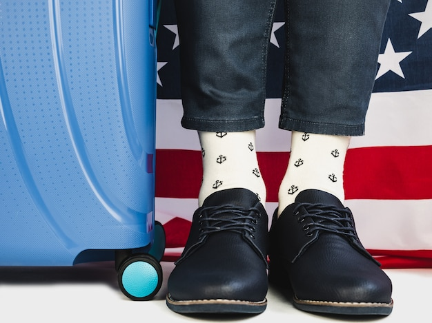 Mala elegante, bandeira dos eua e pernas masculinas