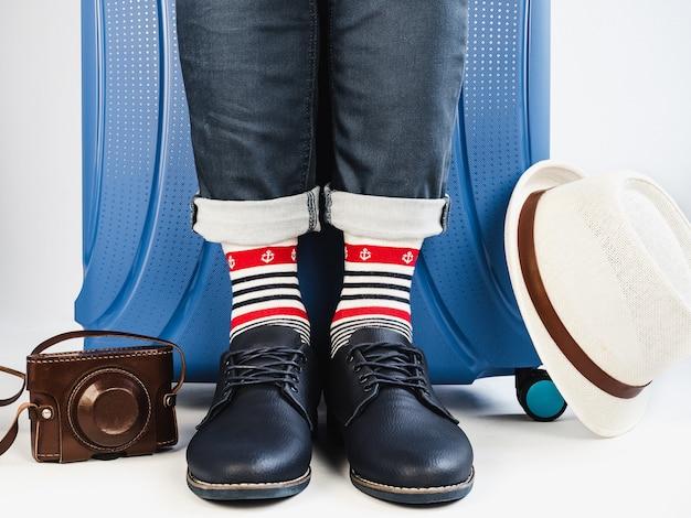 Mala elegante, pernas masculinas e meias multicoloridas