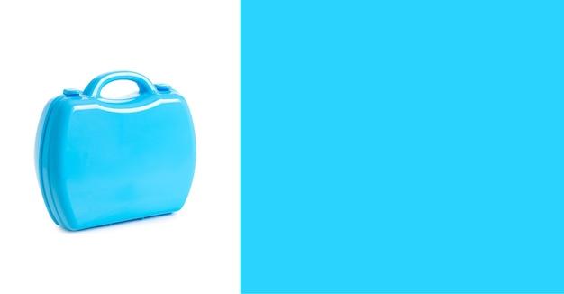 Mala médica de plástico de brinquedo azul sobre fundo branco e azul. espaço livre para texto