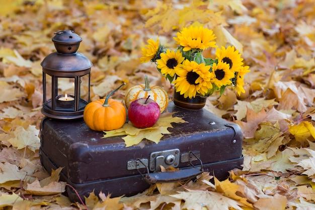Mala velha, sobre ele é um buquê de girassóis em um vaso, duas abóboras, uma maçã e uma lanterna velha