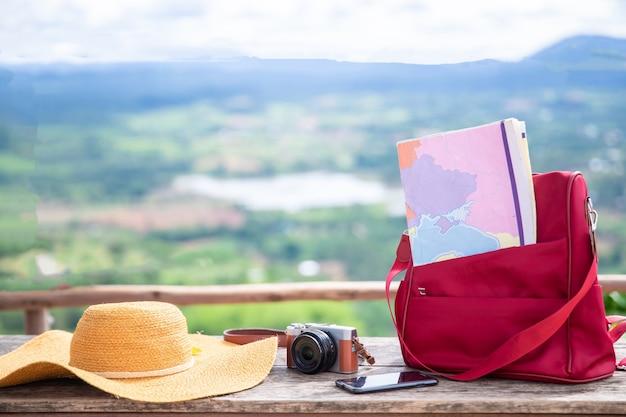 Mala vintage, chapéu moderno, câmera fotográfica e passaporte em deck de madeira.