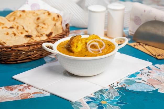 Malai kofta curry na tigela em fundo branco. malai kofta é um famoso prato da cozinha indiana com bolinhos fritos de batata, paneer e queijo em molho de tomate e cebola com especiarias indianas picantes