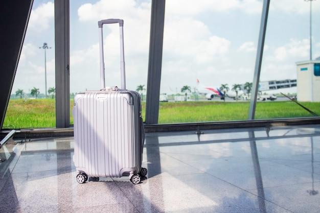 Malas de viagem / bagagem / bagagem em frente ao avião em pista no aeroporto. conceito: transporte e viagens.
