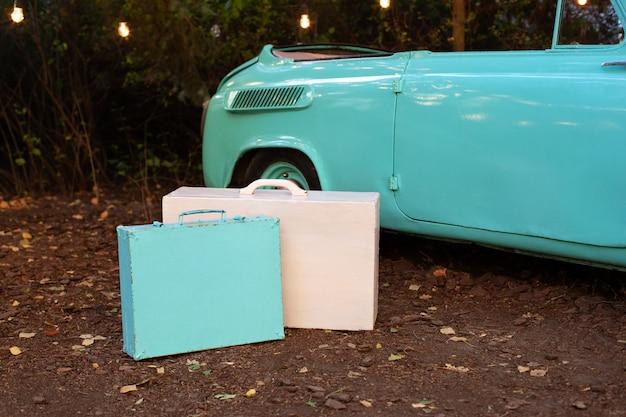 Malas de viagem velhas clássicas do vintage pelo carro que está no jardim. uma mala de madeira azul e rosa está de pé no carro retrô. viagem de verão. conceito de viagens. decoração de casamento. decoração da casa, jardim para férias.