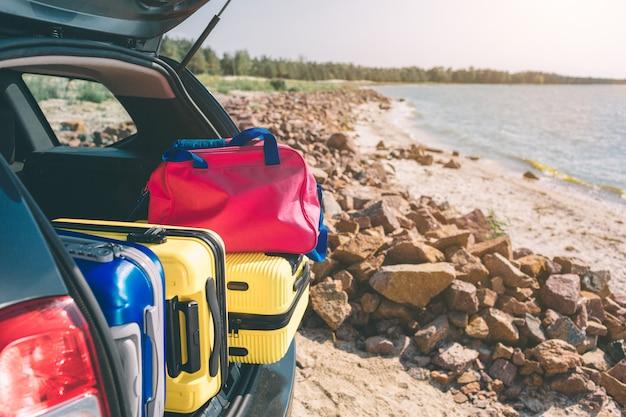 Malas e sacos no porta-malas do carro pronto para partir para férias. movendo caixas e malas no porta-malas do carro, ao ar livre. viagem, viagem, mar. carro na praia com o mar em fundo