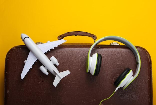 Malas velhas, fones de ouvido e estatueta de avião na superfície amarela