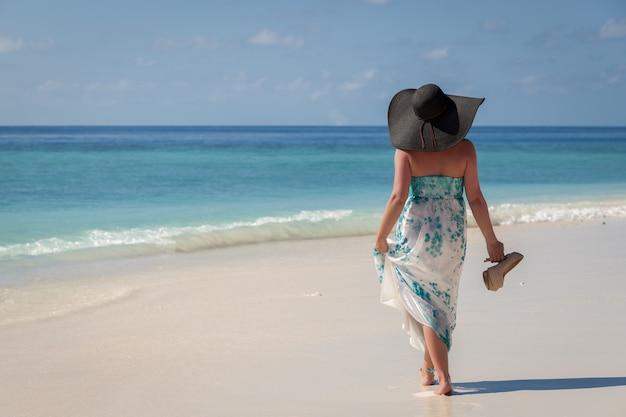 Maldivas, jovem mulher caminhando na praia com chapéu de sol e sapatos de salto altos na mão