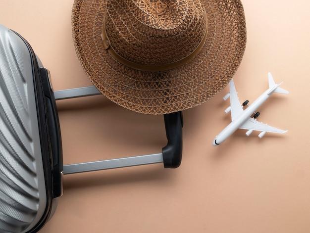 Maleta cinza plana leigos com chapéu marrom e mini avião