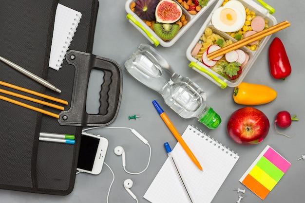 Maleta preta com telefone e fones de ouvido, garrafa de água, cadernos com canetas e lancheira de frutas