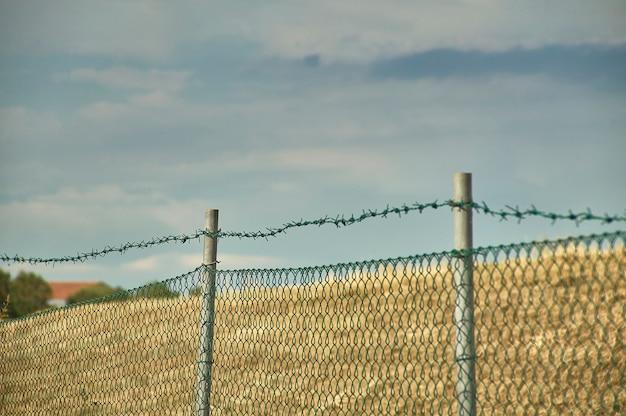 Malha de arame e arame farpado com macro shot e ao fundo o azul do céu, ideal como textura, e como sensação de desejo de liberdade.