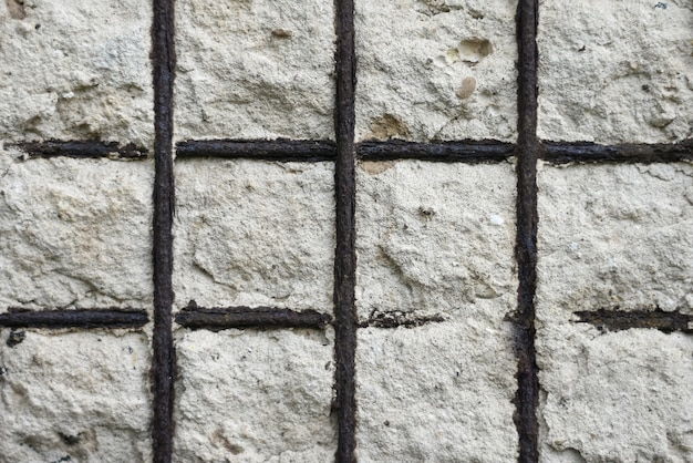 Malha de metal velha de fundo em uma parede de concreto de um edifício