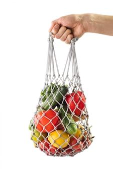 Malha de sacola de compras com legumes saudáveis. desperdício zero. a mão segurando o saco com produtos de malha.