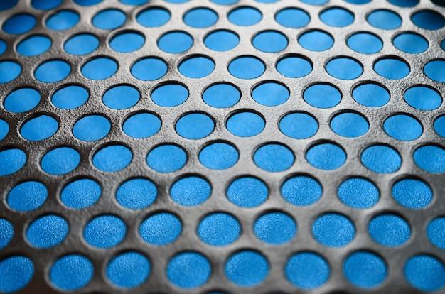 Malha preta do painel da caixa do computador do metal com furos no fundo azul.