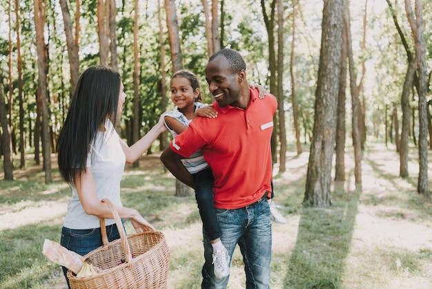 Mamã com balde de piquenique. pai com a filha nas costas.