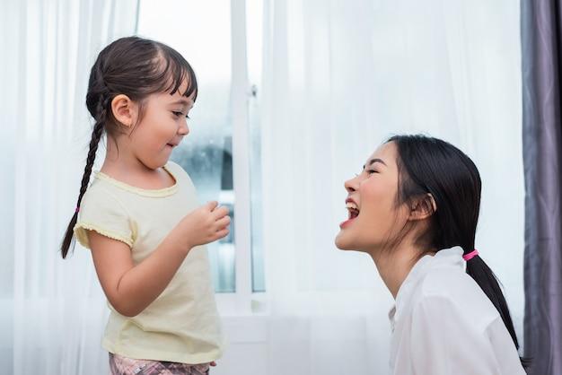Mamã de alimentação da filha com a microplaqueta de batata engraçada. de volta à escola e conceito de educação