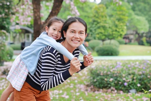 Mamã de sorriso que leva sua menina da criança pequena no jardim.
