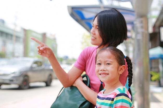 Mamã e filha asiáticas no ônibus do transporte público que apontam algo à vista da menina da criança.