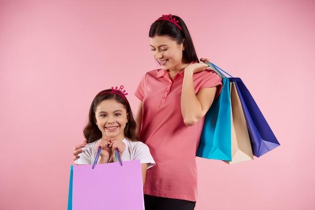 Mamã e filha bonitas na roupa ocasional com sacos de papel.