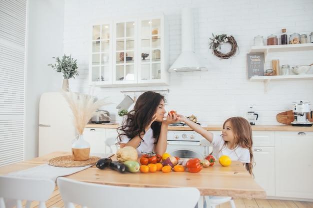 Mamã e filha de sorriso que cozinham frutas e legumes na cozinha do escandinavo-estilo.