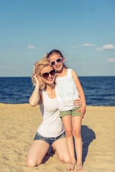 Mamã e sua filha pequena bonito em vidros de sol.