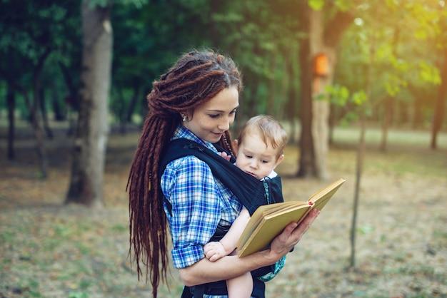 Mamã feliz com um bebê em um estilingue que lê um livro no parque.