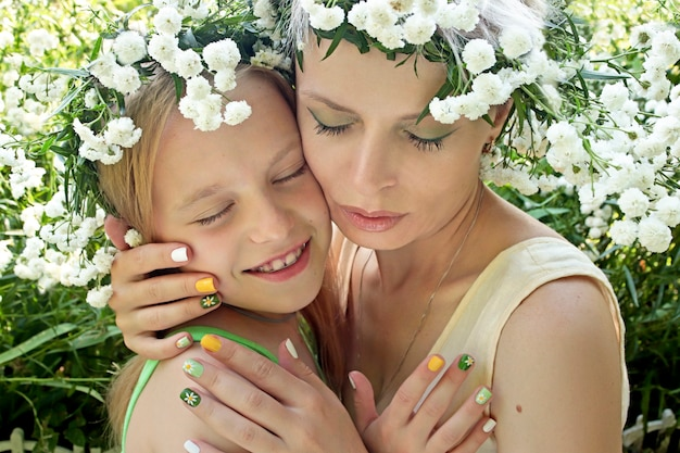 Mamãe abraça a filha em um cenário de flores no verão