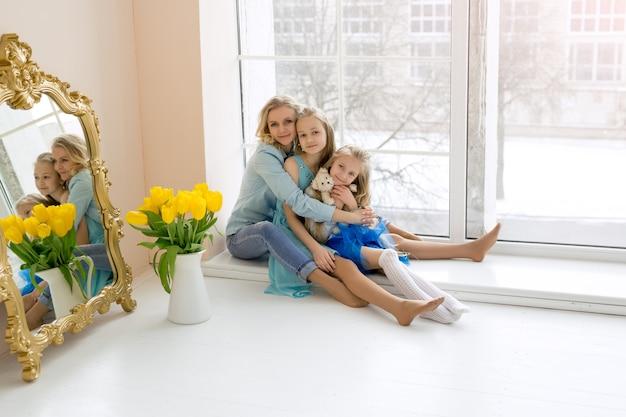 Mamãe abraça suas filhas sentadas na janela