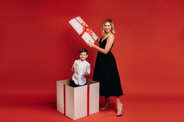 Mamãe abre um enorme presente de natal em que um menino está de pé e mostra a classe sobre um fundo vermelho