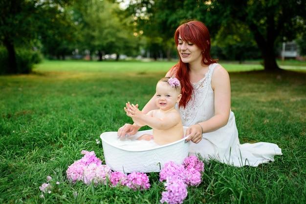Mamãe ajuda sua filhinha de um ano a se banhar no banheiro.