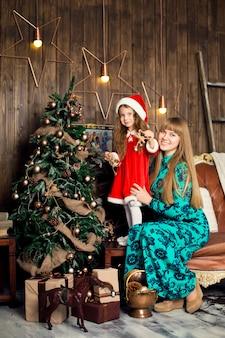 Mamãe ajuda uma garotinha com uma fantasia de papai noel a decorar a árvore de natal. atmosfera familiar e festiva.