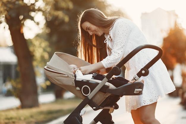 Mamãe andando na rua da cidade. mulher empurrando seu filho sentado em um carrinho de bebê. conceito de família.