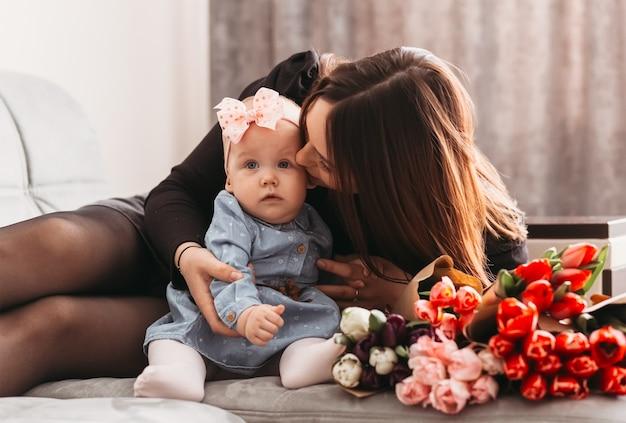 Mamãe beija uma filha bebê na cama com um grande buquê de flores tulipas. dia das mães