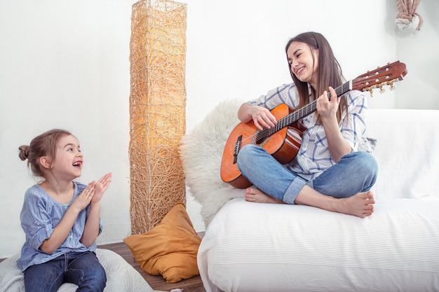 Mamãe brinca com as filhas em casa. aulas de instrumento musical