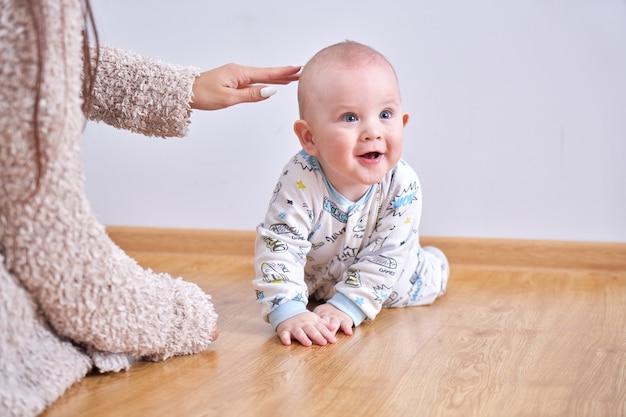 Mamãe brinca com o filho pequeno em casa no chão, ensina a engatinhar, primeiros passos da criança, família feliz