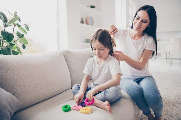 Mamãe carinhosa faz o corte de cabelo de sua filhinha em um apartamento dentro de casa