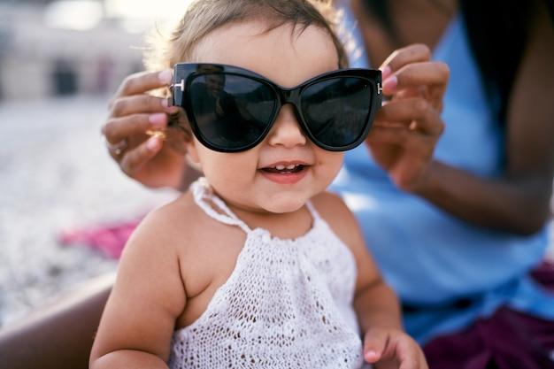 Mamãe coloca grandes óculos de sol em uma garotinha entusiasmada