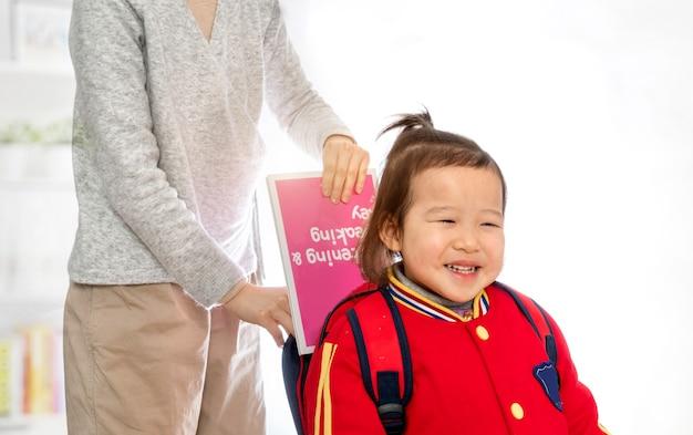 Mamãe colocou o livro na bolsa da menina
