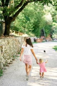 Mamãe conduz uma menina pela mão ao longo do caminho de cascalho no parque