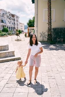 Mamãe conduz uma menina por uma estrada pavimentada com casas ao fundo