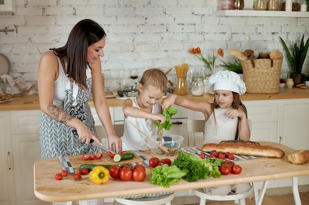 Mamãe cozinha o almoço com as crianças