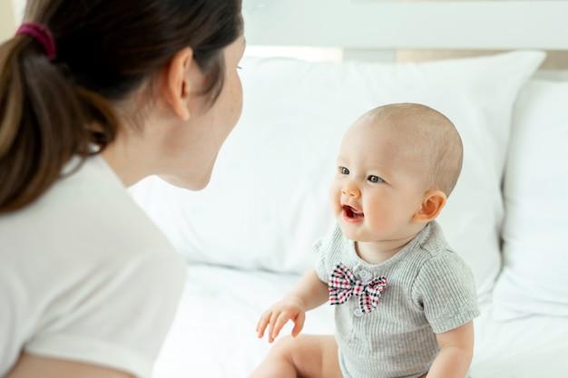 Mamãe e bebê se provocam alegremente em uma cama branca.