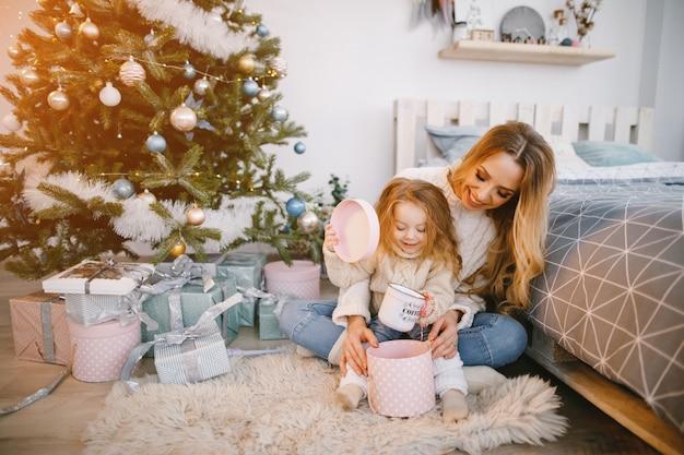 Mamãe e filha que abre presentes